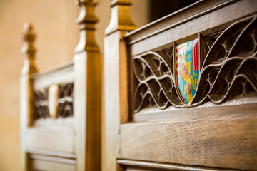 coat of arms inlaid in some intricate wood carving in a chair made for royalty at stirling castle, scotland