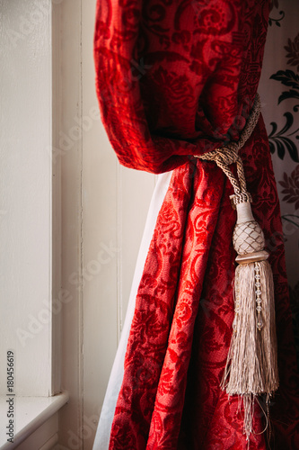gathered red velvet curtains with gold tassel in a rustic