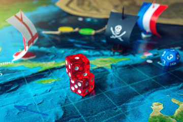 Red playing bones on the world map of the field handmade Board games with a pirate ship