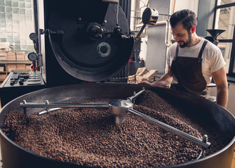 Side view smiling unshaven worker watching at coffee beans situating in grain chiller. Industry...
