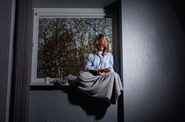 Sad woman by the window.