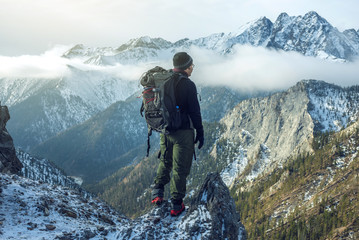 Man hiker with backpack on top of the mountain back, looking at the snow slope. Concept motivation and goal achievement Wall mural