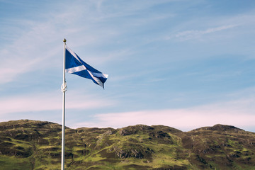 the scottish flag waves in the wind with typical highland scenery in the background