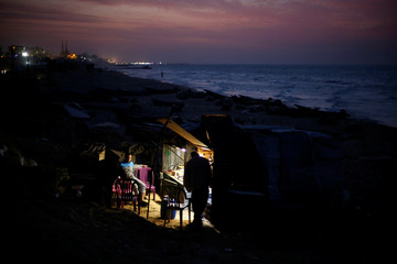 A Palestinian man sits outside a shop on the beach of Gaza City