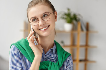 Close up portrait of cheerful beautiful female wears round spectacles, talks on smart phone with old friend, glad to hear her after long time, agree about meeting. Busy office worker has business talk