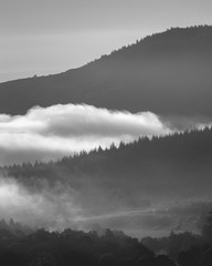 Early morning fog and mist between rolling hills in the Scottish Highlands