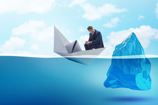 Economic crisis concept with businessman in sinking paper boat