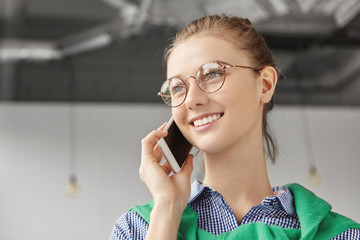 Cheerful European woman has talk on smart phone, wears glasses, looks happily aside, discuss interesting topic with interlocutor. Attractive female uses modern electronic device for communication