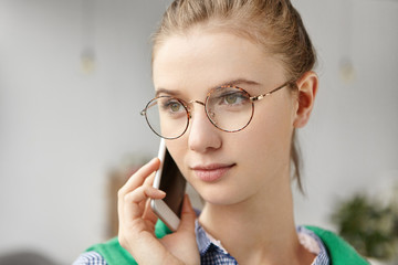 Close up portrait of serious female with healthy skin, charming eyes, wears round spectacles, has business conversation over smart phone, looks aside. People, communication, technology concept