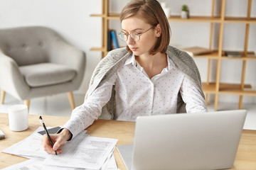 Business and office concept. Successful female enterpreneur sits at wooden table, writes in documents, works hard to achieve her business goals or aims, types on laptop computer. Job and work