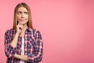 Let me think. Doubtful pensive woman with thoughtful expression, presses lips together, keeps hand under chin, plans something or makes choice, poses against pink background with copy space for text