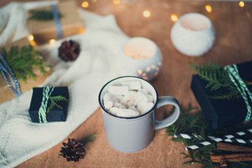Cup of hot coffee with marshmallows, christmas lights, gift boxes, candles