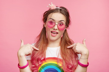 Self assured confident female chick indicates at herself, boasts of her appealing appearance and style, poses against pink studio background. Cute adorable female model with pony tails in sunglasses