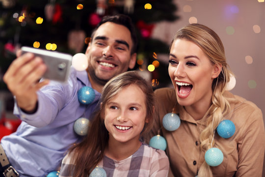 Happy family having fun during Christmas time and taking selfie