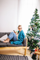woman browsing on her smartphone, while sitting on a comfy couch