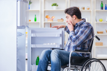Young disabled injured man opening the fridge door