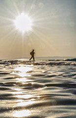 man walks on the ice of lake Baikal and the sun