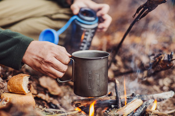 hunter pours water from a bottle into a metal mug.
