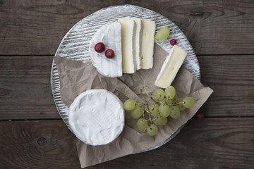 camembert cheese, grape and cranberry on the wooden table