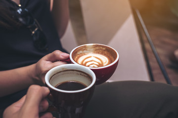 Closeup image of two people clinking coffee cups in modern cafe