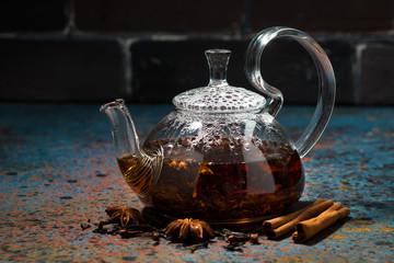 tea masala in a glass teapot on a dark background