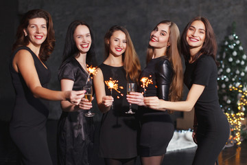 Beautiful girls in evening dresses with glasses of champagne to celebrate the New year