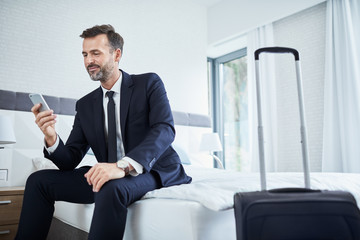 Smiling man using phone in hotel room during business trip
