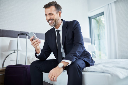 Cheerful businessman using phone sitting in hotel room on business trip