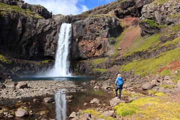 Hiker at waterfall in Iceland / Wanderer an einem Wasserfall in Island