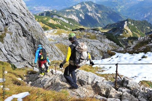 Klettersteig Outfit : Bergsteiger auf dem abstieg vom gipfel über einen klettersteig am