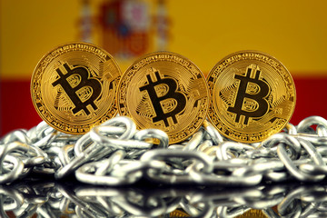 Physical version of Bitcoin (new virtual money), chain and Spain Flag. Conceptual image for investors in cryptocurrency and Blockchain Technology in Spain.