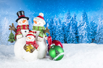 Christmas decoration with snowman figurines as a family, red baubles on a blue snow pine tree landscape background