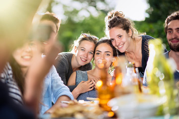 young women lunching on a terrace with friends pose for a photo