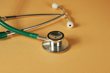 Stethoscope on orange background.