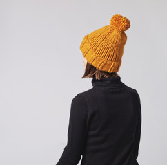 Woman wearing mustard knit beanie hat with big pom pom and black turtleneck isolated on grey background. Copy space