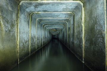 Dark and creepy flooded underground sewer concrete tunnel. Industrial wastewater and urban sewage flowing throw the tunnel