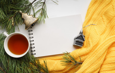 Christmas background with a Cup of tea, a notebook, branches of pine with large needles and a yellow sweater. Top view