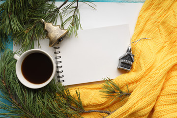 Christmas background with a Cup  of coffee, a notebook, branches of pine with large needles and a yellow sweater. Top view