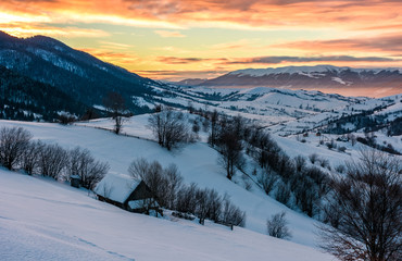 winter dawn in mountainous countryside. gorgeous cloudy sky over the snow covered hills. wide mountain ridge in a far distance