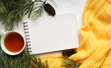 Christmas background with a Cup of tea, a notebook, fir cones, branches of pine with large needles and a yellow sweater.