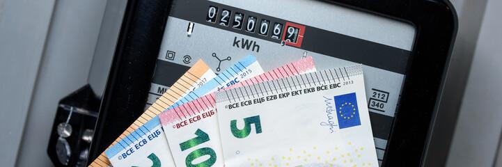 Stromzähler mit Geldscheinen im Vordergrund