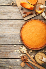 Pumpkin tart with honey, sugar and seeds on wooden table