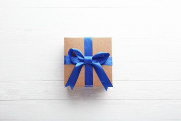 Brown gift box with ribbon on white wooden table