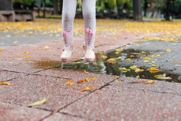 Girl jumping in a puddle