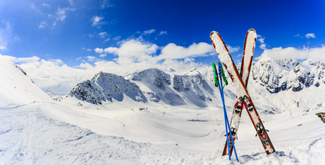 Wall Mural - Ski in winter season, mountains and ski touring backcountry equipments on the top of snowy mountains in sunny day. South Tirol, Solda in Italy.