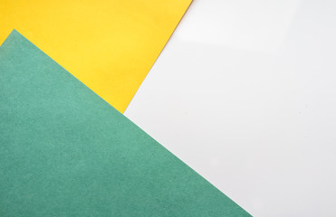 The composition of the colored sheets of paper. Geometric background. Bright typographic design  Top view, close-up