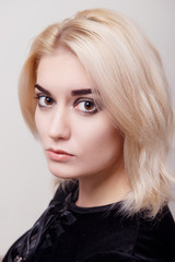 Blonde girl with bright makeup and clean skin on a white isolate close-up