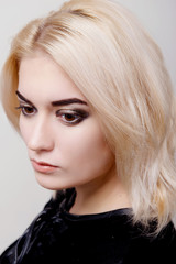 Blonde girl with bright makeup looking down on the white isolate close-up
