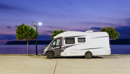Motorhome RV and campervan are parked on a beach. Motor home caravans are parked on a parking space for RV vehicles by Aegean sea in Greece. Night scenery.