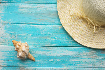 Straw hat and a  seashell on a painted blue paint vintage boards The top view. Close-up